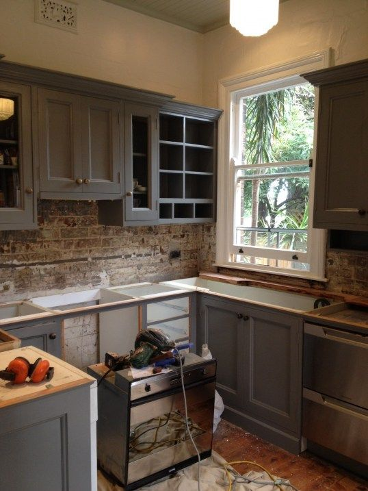 I know this is a renovation progress shot but I really like the exposed brick with that cabinet color