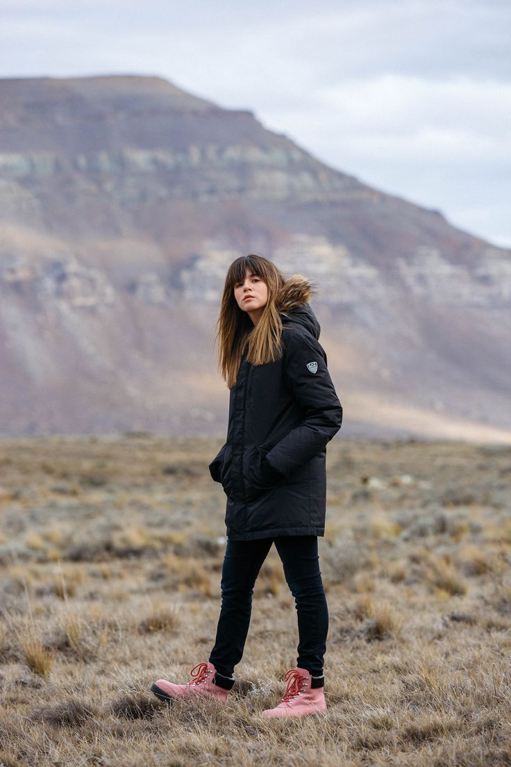 Maristella wears a black parka and skinny jeans with pink Acne boots in El Calafate, Argentina