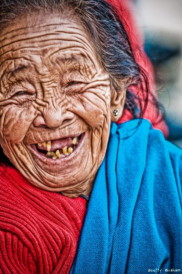 """Wow, pull out the colored pencils and try to capture this lady.  she is beautiful!  """"I was walking down a street in Kathmandu, and I saw this lady just laughing like there was no tomorrow while sitting on a wood bench...I have no idea what she was laughing about, but she loved to have her photo taken...which is actually unusual in Nepal as most older people do not like to have their photo taken. What a face....and what a smile!!"""" —Scotty Graham/Last Flight Out Photography"""