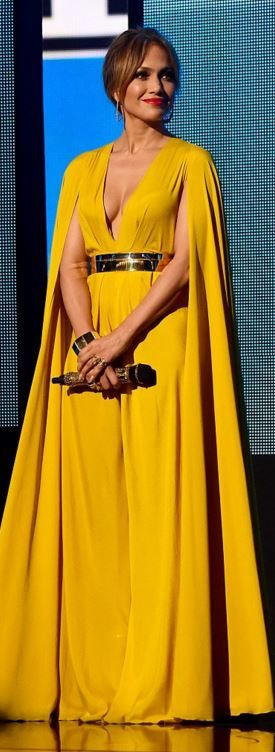 Who made  Jennifer Lopez's yellow gown and gold jewelry?