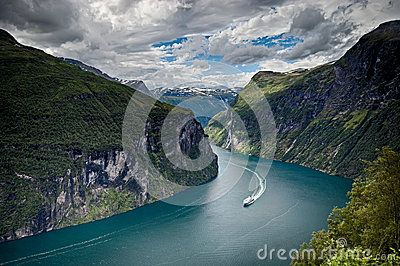 A view on the most beautiful fjord in Norway, Geirangerfjord. A huge ferry boat on the fjord from this distance appears to be very small. HDR image.