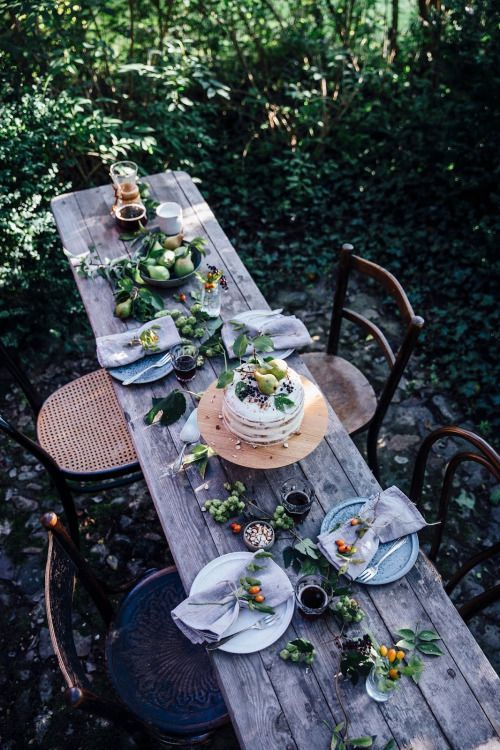 Beautiful outdoor dining setting with wooden table and rustic vintage wooden chairs.