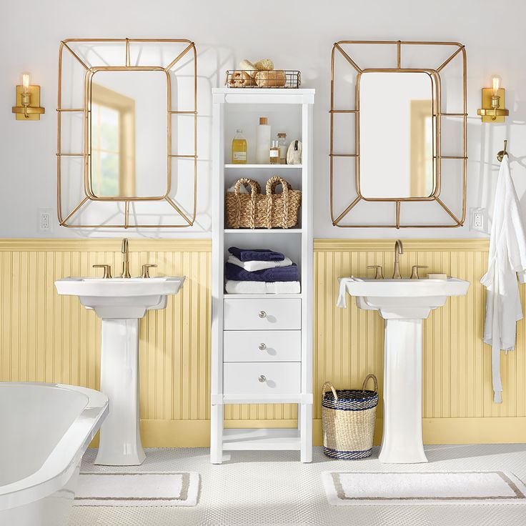A bathroom with two sinks and headboard wainscoting
