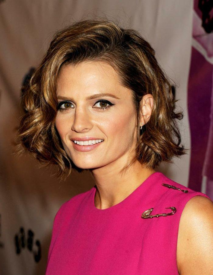 cortes de pelo rizado mujer con blusa rosa pelo ondulado con raya ladeada