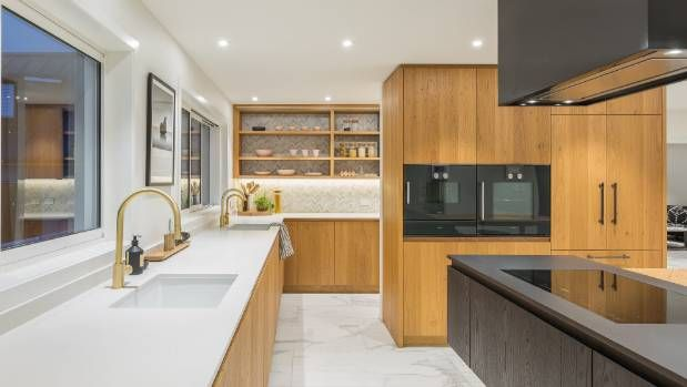 The induction hob and rangehood are Miele appliances. The designer also provided two fireclay butlers' sinks, one at the ...