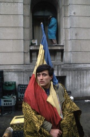 Romanian man in the midst of the 1989 revolution wears a blanket for warmth and carries a symbol of the revolution, a Romanian flag with the Communist emblem torn out of the center.