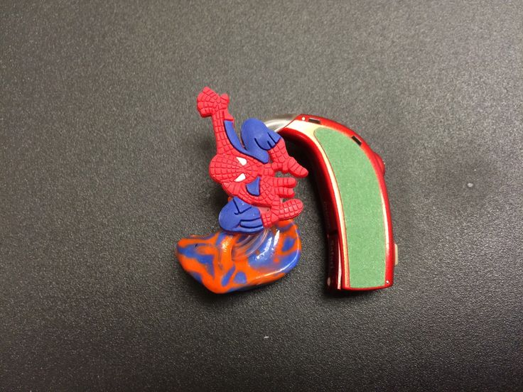 Orange and blue earmold, red hearing aid and Spider-Man tube rider