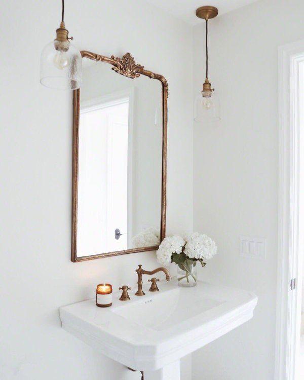 Gold antique mirror above bathroom sink