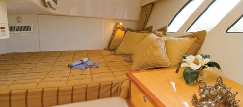 """Intrepid 475 Sport Yacht: The master stateroom has a queen athwartships berth, triple hull-side windows, 6'8"""" (2 m) of overhead clearance and a deck hatch for light, ventilation, and emergency egress. There is also a separate access to the head."""
