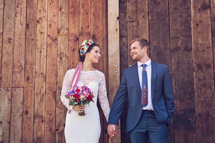 Folková nevěsta v krajkových svatebních šatech s louhými rukávy se ženichem v modrém obleku.