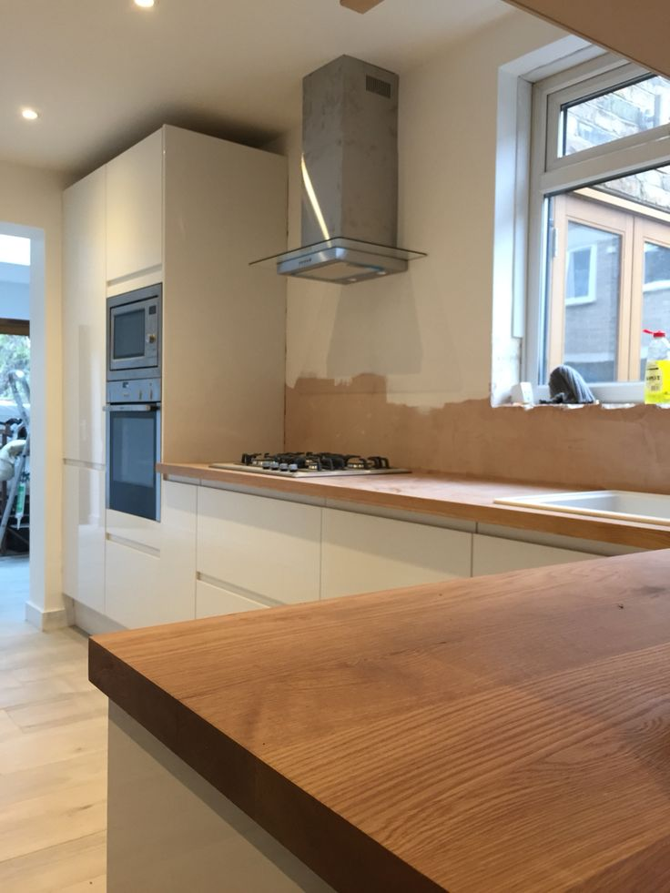 Kitchen progress.  Howdens white gloss handless units with solid full stave rustic oak worktops. Off white wood effect porcelain floor tiles.