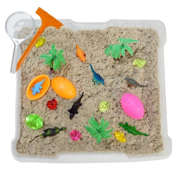 Dinosaur World Discovery Boxes by Revelae Kids introduce kids to a magical world of realistic-looking dinosaurs, neon dino eggs, sparkling gems and crystals, and colorful palm trees within an closeable sensory bin.
