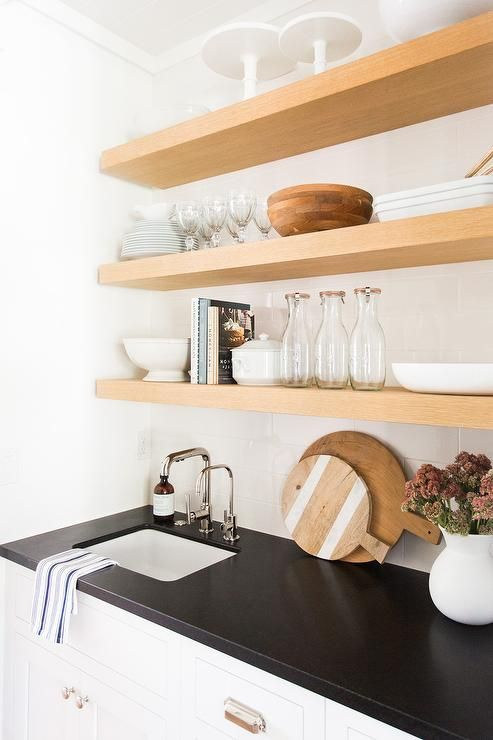 Blond floating shelves are mounted on staggered white tiles above a white butler's pantry cabinets fitted with polished nickel cup pulls and a black granite countertop holding a curved square sink paired with polished nickel faucet kit.