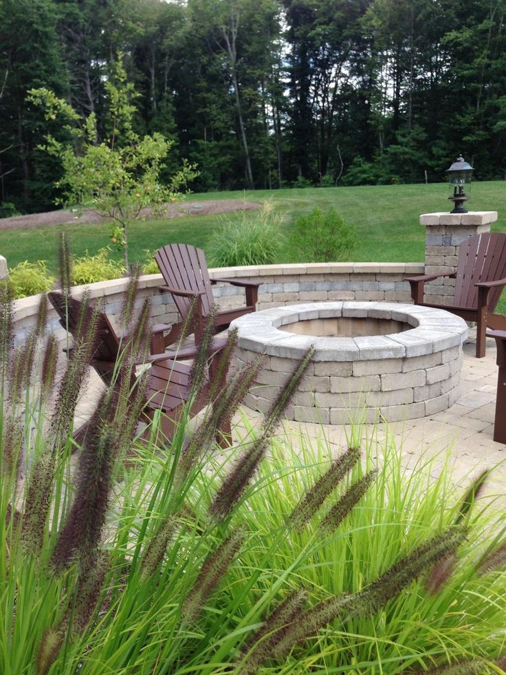 A stacked brick fire pit is surrounded by comfortable Adirondack chairs to create a cozy outdoor living space. Columns and a garden wall help to define the area from the rest of the backyard, which features native plants and ornamental grasses.