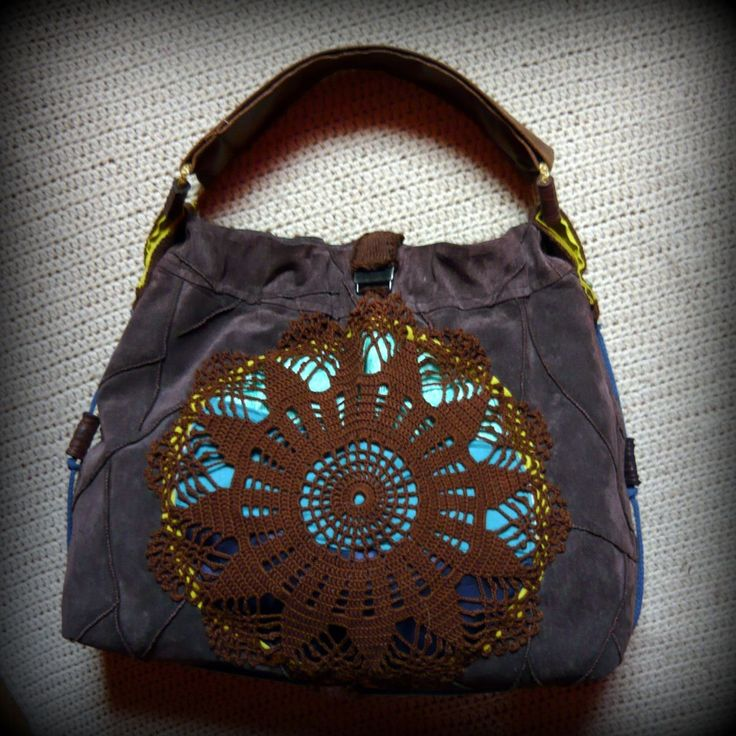 Barna bőrtáska -Handmade by Judy Majoros: Barna bőrszoknya az alapja ennek a táskának. Csipkével, 3 különböző kék textillel, gyapjú kötött szalaggal, gyönggyel, és zsinórral díszítettem.Hátsó részén kézzel készített pamut bojt díszíti.  Vállpántja textilbőrből készült. Bélése barna selyembélés rajta egy 15x20 cm-es zsebbel. Tetején kapoccsal záródik.
