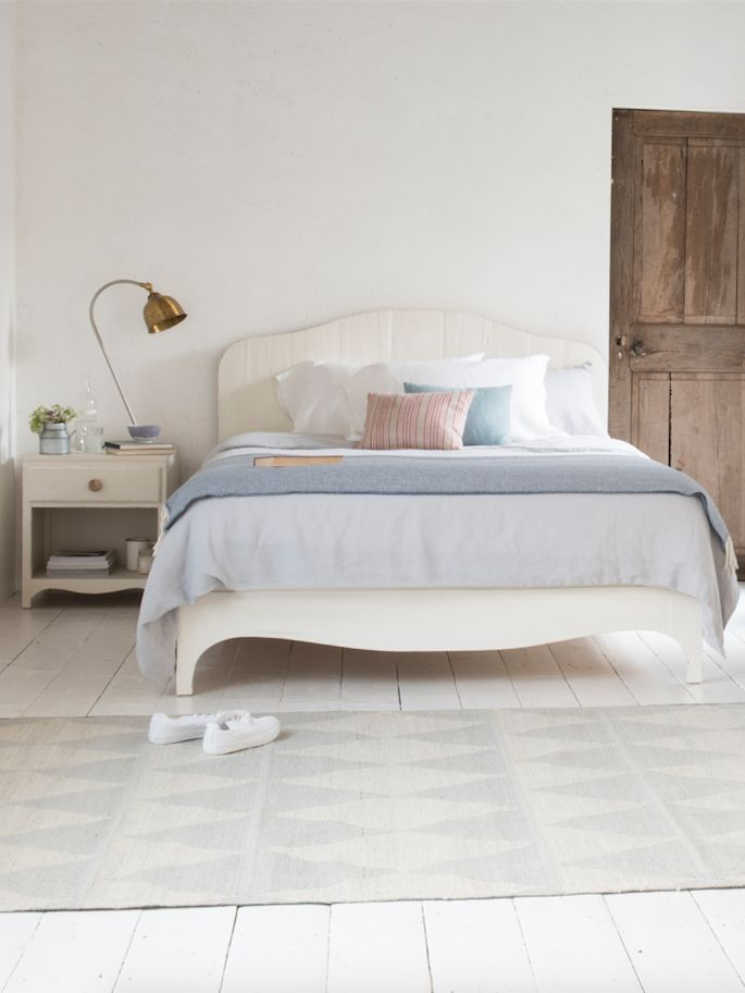 Loaf's white painted wooden Barnstorm bed in this scandi bedroom with light grey linen sheets and a rustic wooden door