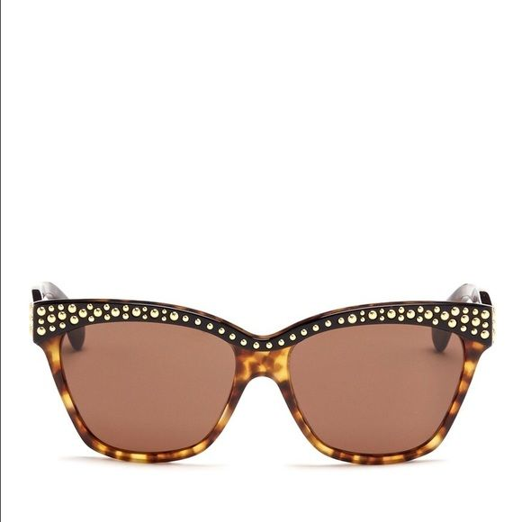 Alexander McQueen Studded Brow Tortoise Sunglasses Saunter a dramatic entrance w/ these tortoiseshell sunglasses from Alexander McQueen. Featuring a contrasting solid black brow bar with gold-tone studs, this pair exudes a rock-meets-sophisticated glamour. Squared cat-eye frame. Translucent brown frame, solid black coating on brow bar and arms, gold-tone round studs on brow bar, gold-tone embossed logo at temple, brown lenses. Made in Italy. Measures: Frame Width 15cm / Frame Height 5.5cm…