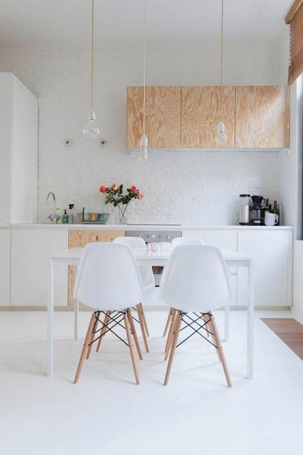 Cozinha branca com detalhes de madeira, cadeiras Eames, luminárias pendentes industriais e muito charme! Veja mais ambientes como este clicando na foto
