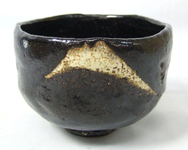 A Raku chawan. Grainy black lacquer is sharply interrupted by a jagged granite-like swoop and sudden rough pock-marks. Prompts meditation on the rugged unconquerable beauty of mountains.
