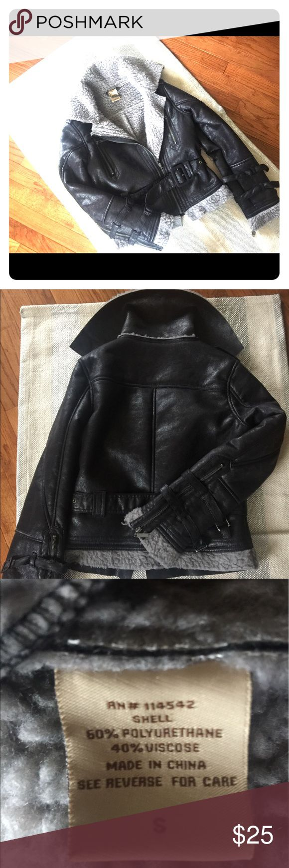 NWOT Jou Jou black leather-looking jacket S Black soft/shimmery exterior, grey wool-like lined interior jacket with zippered & buckled wrists & belt buckles waist.  Gun-metal colored hardware, 2 vertical zippered breast pockets.  I ripped the tags off intending to wear it out one night but ended up wearing something else instead, so it's actually never been worn at all.  No stains, odors, rips, etc.  New, cute, and won't crack/dry rot/look cheap the way pleather does.  It's exterior is…