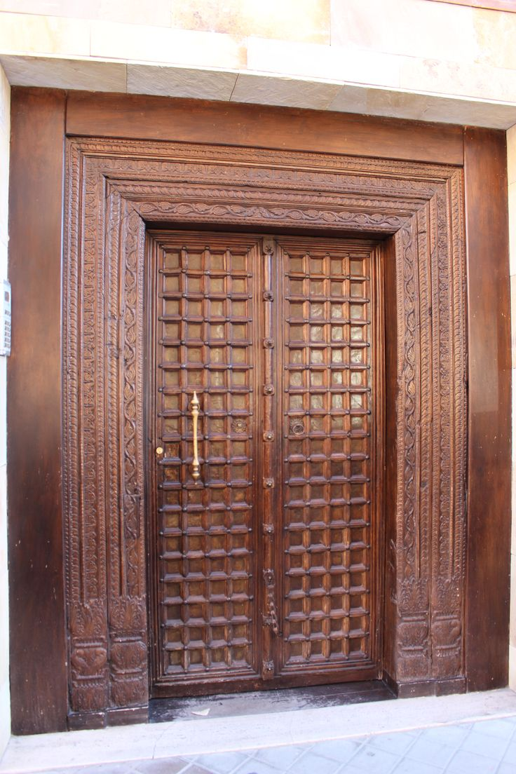Puerta de reminiscencias mudéjares en edificio contemporáneo.