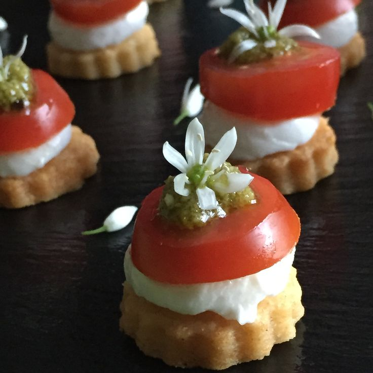 Parmesan biscuits, topped with halves of mini mozzarella, topped with homemade wild garlic pesto and garnished with garlic flowers. Easy to make but ever so elegant on a canapés platter