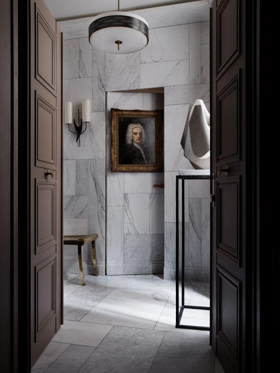 Dans l'entrée, une sculpture de Philippe Angot (Onsite Antiques) accueille les visiteurs. La porte qui mène à la cuisine est dissimulée derrière le mur en faux marbre réalisé par Mathias Kiss.