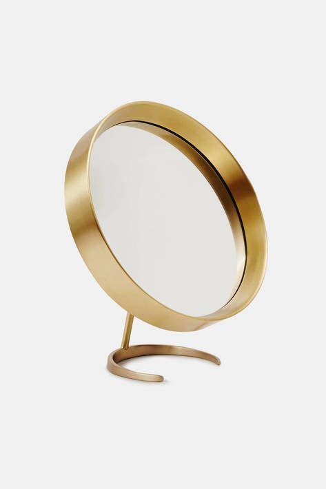 Tenfold New York bridges the definitions of a house and a home: a place of both function and beauty, revelation and intimacy, ritual and amenity. This satin-finished brass mirror is a versatile addition to any vanity, table, or countertop. Designed to pivot atop a streamlined stand, it can be positioned at various angles on either side of the semi-circular base.