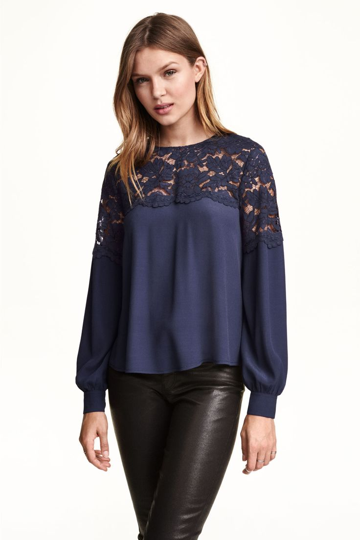 Blusa com escapulário de renda: Blusa de tecido crepe com escapulário de renda, mangas compridas, botões nos punhos e na parte de trás do pescoço e base arredondada.