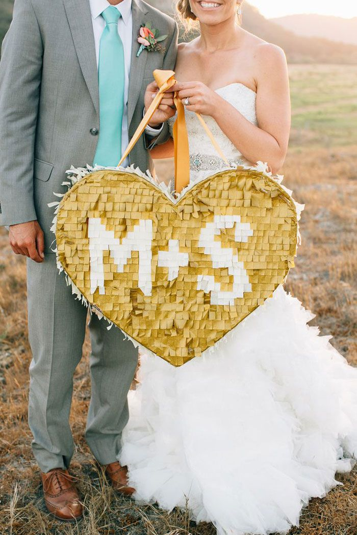 A gold heart shaped piñata with initials. Source: stylemepretty.com #piñata #gold #receptionideas