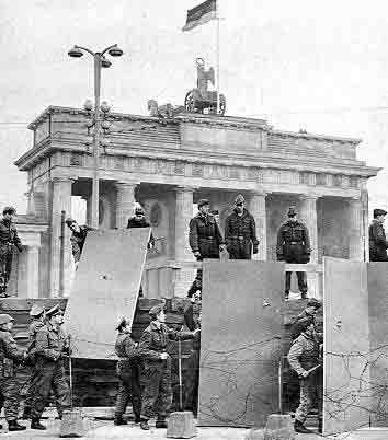 hier zie je de soldaten bouwen aan de Berlijnse muur. Ze bouwen de muur met grootte stenen en prikkeldraad.