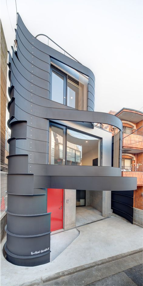 Clad in curved and patinated steel ribbons, the house spans three levels above ground. The size of the stacked elements decreases as the height increases, which creates an especially dynamic facade