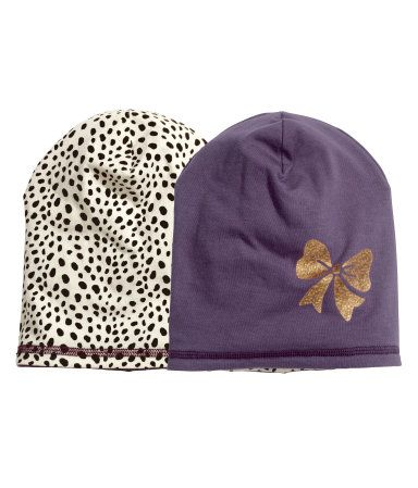 Reversible hat in double-layer jersey. One patterned side and one solid-color side with a printed motif.