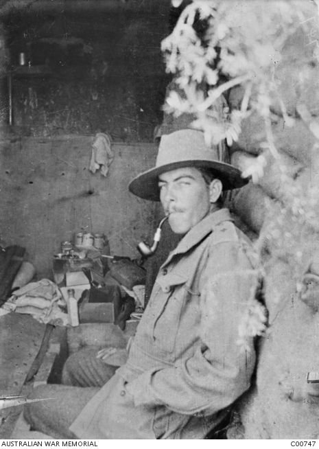 WWI, 1915, Gallipoli. An unidentified Australian officer smoking a pipe inside his dugout on the Gallipoli Peninsula.  Note that he has his badge of rank pencilled on his epaulette.  This practice was largely adopted by officers and non commissioned officers after the landing on 25 April 1915, probably because of a desire not to be conspicious to the enemy.