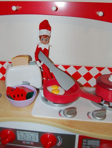 Elf making the kids breakfast in their play kitchen.