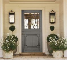 White siding, grey door with glass accents, symmetrical planters and wall lanterns