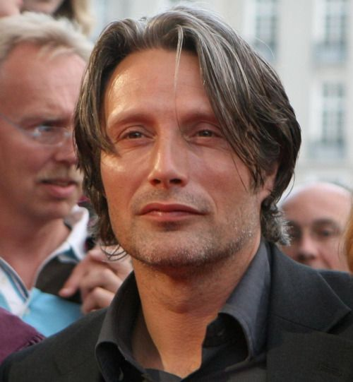 : Seeing Mikkelsen off screen is a bit of a shock. First, he has two eyes, neither of which is oozing blood. Second, he looks like a rippling Hollywood stud. More Bond than Bond villain, you might say. The first sight I catch of him is outside the London hotel where we're meeting. Mikkelsen is standing in a doorway, tanned and tall, wearing a leather jacket and jeans and puffing on a cigarette. He has a startlingly handsome, wolfish face: crafty eyes, cheekbones so chiseled you could cut…