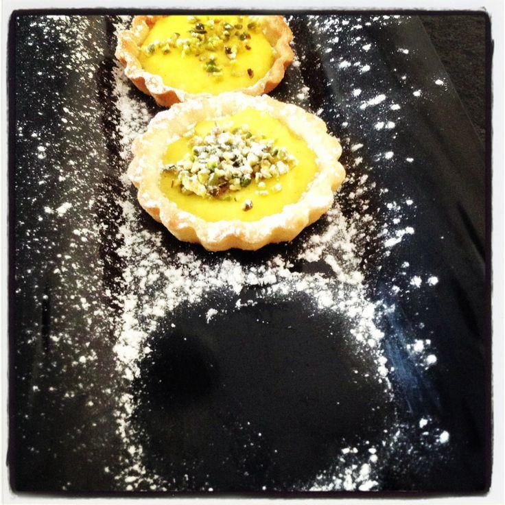 Tartellette con crema pasticcera e granella di pistacchi.