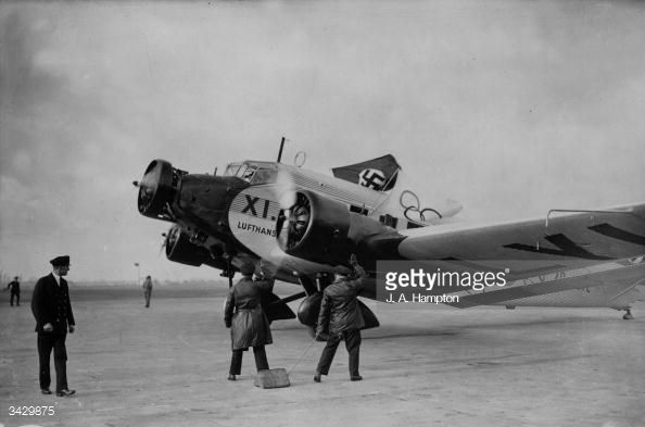 2nd December 1935: Employees of Deutsche Lufthansa air line giving a Nazi salute as a plane flying a Nazi flag and carrying the German Olympic Games Committee lands at Croydon Aerodrome. The plane is a Junkers Trimotor or Junkers Ju 52. (Photo by J. A. Hampton/Topical Press Agency/Getty Images)