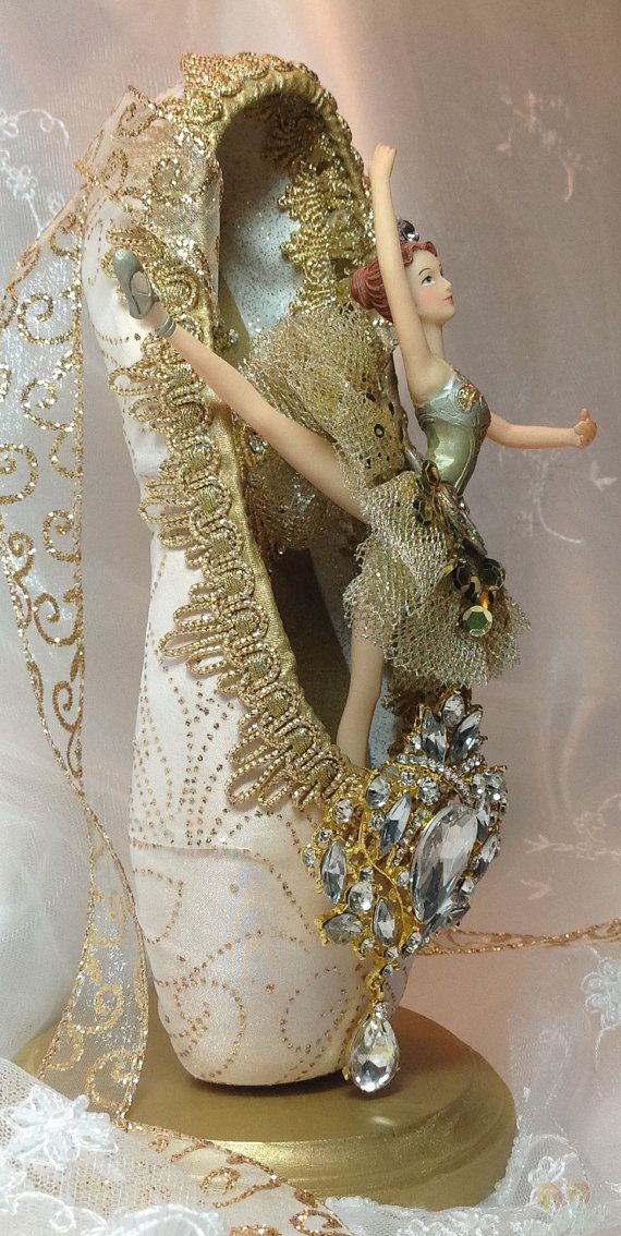 Spectacular ivory and gold ballerina centerpiece featuring a Kurt Adler ornament and an equally spectacular rhinestone brooch. This freestanding centerpiece deserves center stage! The new pointe shoe was painted ivory then covered with organza fabric that has gold sparkly swirls. The toe box is almost totally covered by the brooch. The inner sole (behind the ballerina) is embellished with gold appliqués highlighted with Swarovski crystals. Would be lovely keepsake for the Sleeping Beauty…