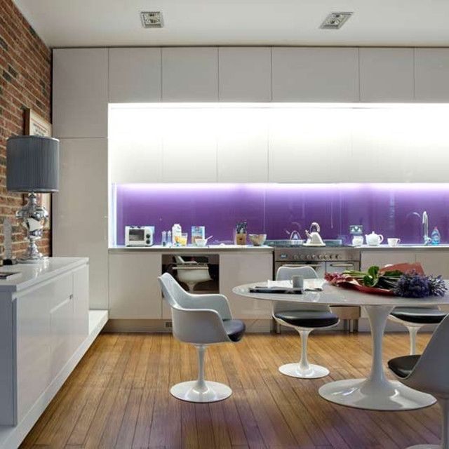 Purple glass splashback, white gloss units, wooden floor