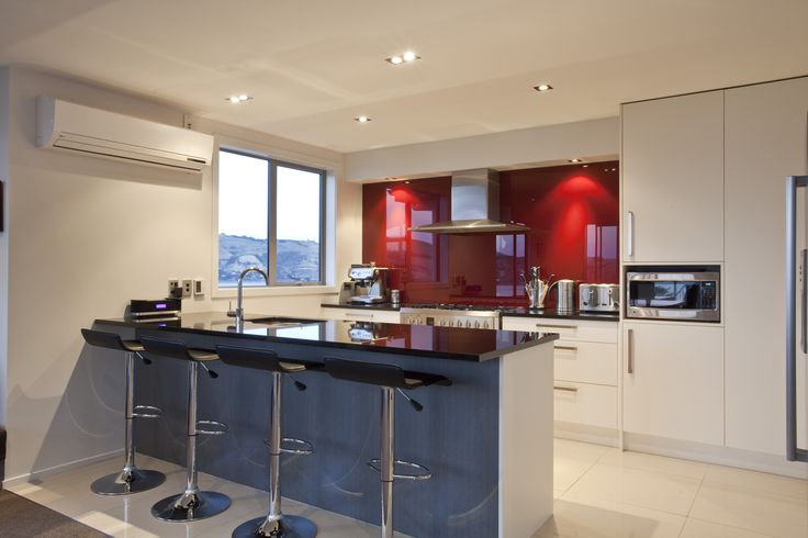 A kitchen punctuated by two vibrant colour blocks on the splashback and below the bench, along with the black stone benchtop, create an amazing space with strong bold colours.