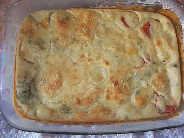 Massa:  - 3 ovos  - 1/2 xícara de óleo  - 2 xícaras de leite  - 2 e 1/2 xícaras de farinha de trigo  - 1 colher (sopa) de fermento em pó  - 3 colheres (sopa) de queijo ralado  - 1 pitada de sal  - manteiga para untar  - farinha de trigo para polvilhar  - Recheio:  - 2 latas de sardinha  - 3 ovos cozidos duros  - 2 tomates bem maduros  - 1 lata de milho verde  - 1/2 cebola cortada em rodelas  - 1/2 xícara de cheiro verde (coentro e cebolinha)  - Queijo ralado para polvilhar  -