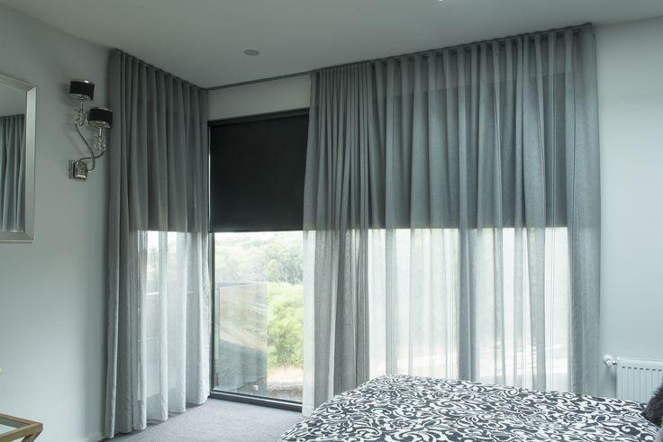 Black roller blinds behind sheer voiles