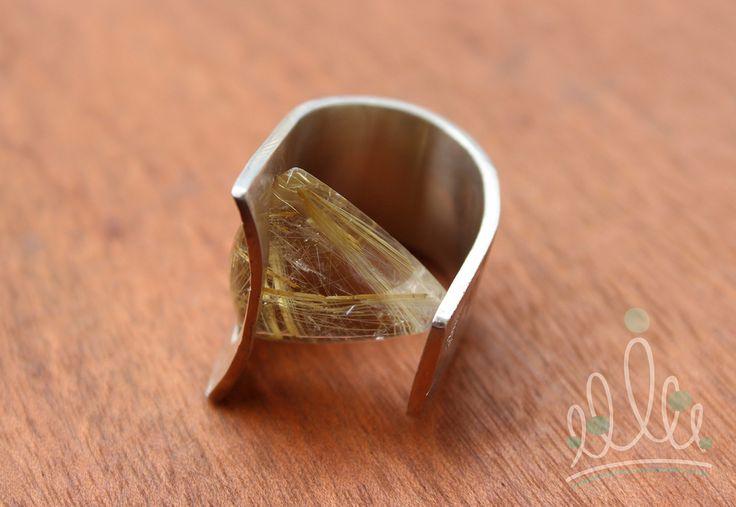 anel de forja em prata texturizada com aplicação de quartzo rutilado triangular em tons dourados, preso sob pressão.