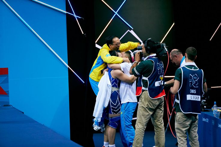 Svetlana Podobedova of Kazakhstan is embraced by her team after taking gold in the women's 75kg weightlifting.