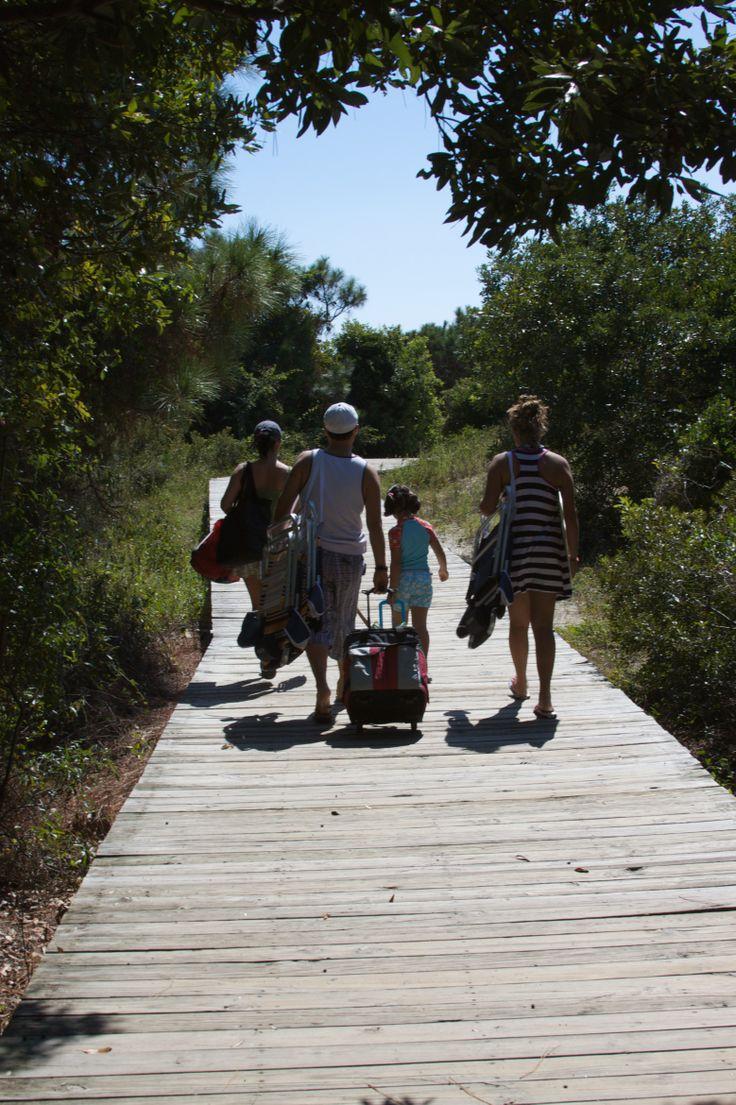 Beachgoers make the short walk from the parking lot to the beach at Beachwalker County Park on Kiawah Island, South Carolina.