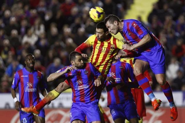 El centrocampistas del FC Barcelona Sergio Busquets (c) lucha un balón ante los jugadores del Levante David Navarro (d) y el griego Loukas V...