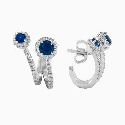Oval sapphires of midnight blue are framed by glittering halos of micropavé set brilliant diamonds and continue to unusual shape in these timeless drop earrings crafted of 18k white gold.Impressive 0.85 ct natural sapphires and 0.45 ct diamonds.