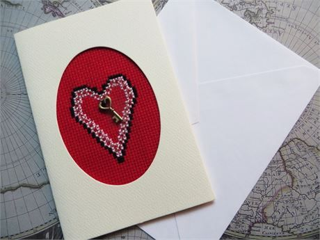 A small handmade card: 3 1/2 by 5 1/2 inches (just under 9 cm x 14 cm)   A heart with beads around the outside and a brass coloured charm inside.